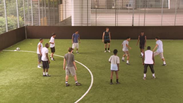 vídeos de stock, filmes e b-roll de ws soccer players in circle passing ball, london, uk - jogador de futebol