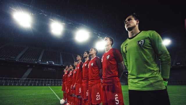 Soccer players in red uniforms at rainy stadium