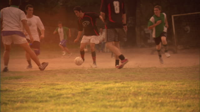 MS, soccer players kicking ball then greeting colleagues on field, Buenos Aires, Argentina