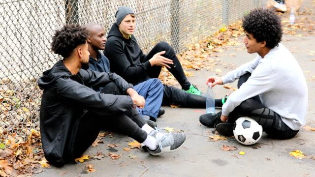 Joueurs de foot parler tout en restant assis contre le guide