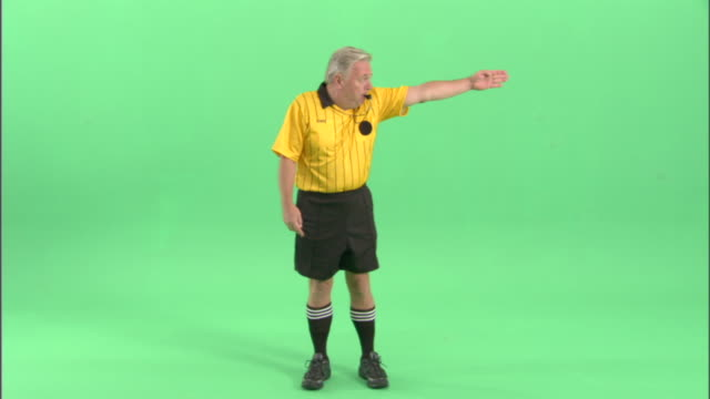 WS, Soccer referee blowing whistle and pointing in studio, portrait