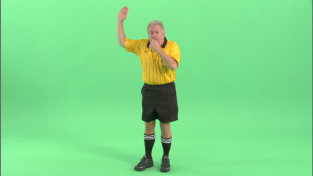 ws, soccer referee blowing whistle and pointing in studio, portrait - one mature man only stock-videos und b-roll-filmmaterial