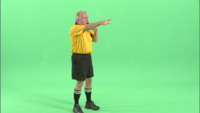 ws, soccer referee blowing whistle and pointing in studio - trillerpfeife stock-videos und b-roll-filmmaterial