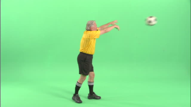 WS, Soccer referee blowing whistle and throwing ball in studio