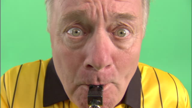 ecu, soccer referee blowing whistle in studio, portrait - trillerpfeife stock-videos und b-roll-filmmaterial