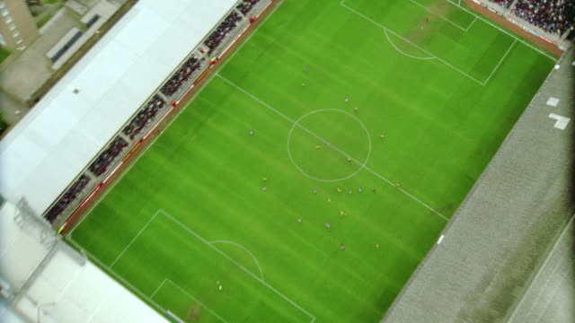 AERIAL soccer stadium during game / zoom in + zoom out of field / West Ham FC, London