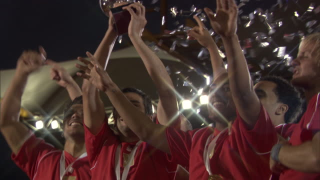la ms soccer team jumping and celebrating with trophy as confetti falls / sheffield, england, uk - vincere video stock e b–roll