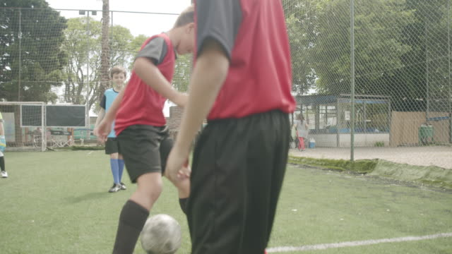 soccer team of kids playing football with their coach - teenage boys stock videos & royalty-free footage