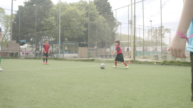 soccer team of kids playing football with their coach - boys stock videos & royalty-free footage