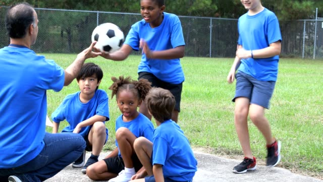 soccer team players sit and listen to coach explain next play. - primary school child stock videos & royalty-free footage