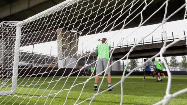 ms soccer team scoring goal, seen from behind goal post, london, uk - カーテン レース点の映像素材/bロール