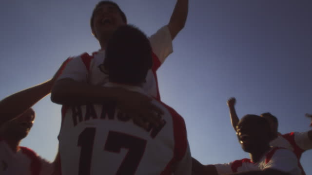 slo mo. soccer teammates celebrate a victory by jumping and hugging each other on a soccer field inside a stadium - winning stock videos & royalty-free footage