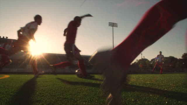 stockvideo's en b-roll-footage met slo mo. soccer teammates run and dribble a soccer ball across a soccer field inside a stadium at sunset - schemering