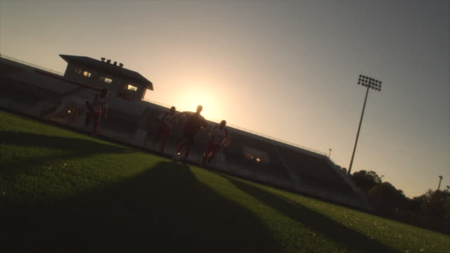 stockvideo's en b-roll-footage met slo mo. soccer teammates run and dribble a soccer ball across a soccer field inside a stadium at sunset - dribbelen
