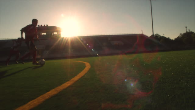 slo mo. soccer teammates run and dribble a soccer ball across a soccer field inside a stadium at sunset - football pitch stock videos & royalty-free footage