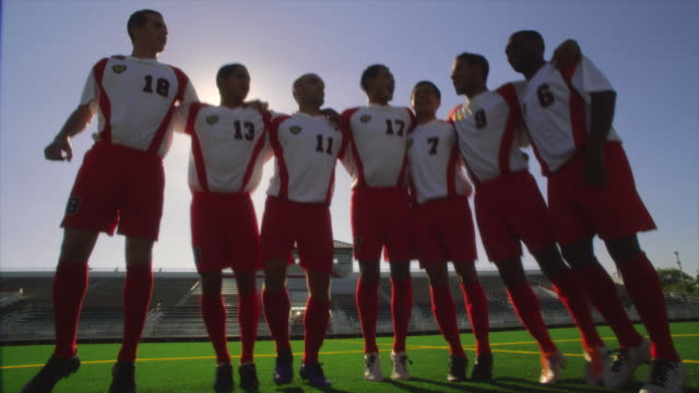 soccer teammates stand in a line with their arms around each other and chant on a soccer field inside a stadium - football strip stock videos & royalty-free footage