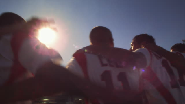 vidéos et rushes de slo mo. soccer teammates stand in a line with their arms around each other and chant on a soccer field inside a stadium with their backs to the camera at sunset - endurance
