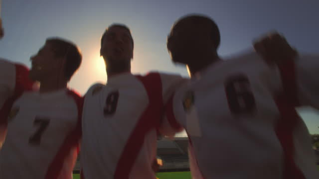 vídeos de stock e filmes b-roll de soccer teammates stand in a line with their arms around each other and chant on a soccer field inside a stadium - amizade masculina