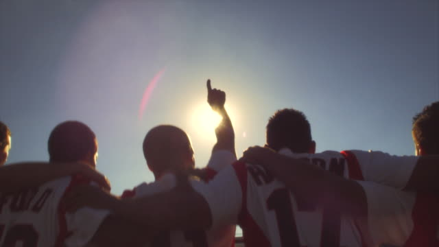 SLO MO. Soccer teammates stand in a line with their arms around each other and chant on a soccer field inside a stadium with their backs to the camera at sunset