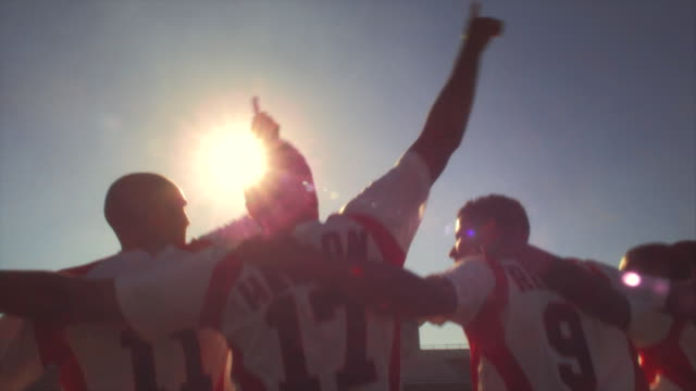 Soccer players jump up and down and chant with their arms around each other.