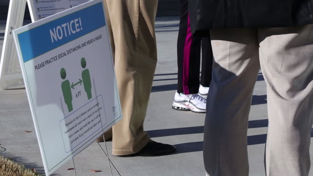 social distancing notice next to people waiting to vote at an early voting location in durham, north carolina, u.s., on thursday, october 15, 2020. - low section stock videos & royalty-free footage