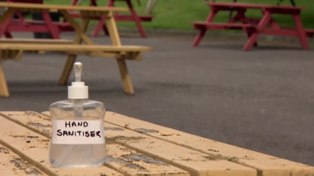 a social distancing sign and hand sanitiser in a pub beer garden - b roll stock videos & royalty-free footage