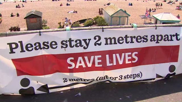 """social distancing sign at brighton beach as people go to the seaside and enjoy the hot weather during the coronavirus pandemic after some lockdown... - """"bbc news"""" stock videos & royalty-free footage"""