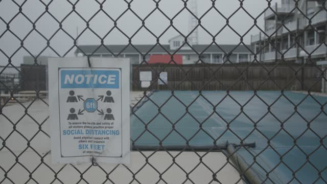 social distancing sign is posted on the fence outside of a closed swimming pool amidst pandemic related restrictions on march 28, 2021 in... - swimming pool stock videos & royalty-free footage