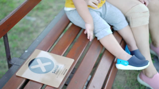 social distancing sign on the park bench at the public park - bench stock videos & royalty-free footage