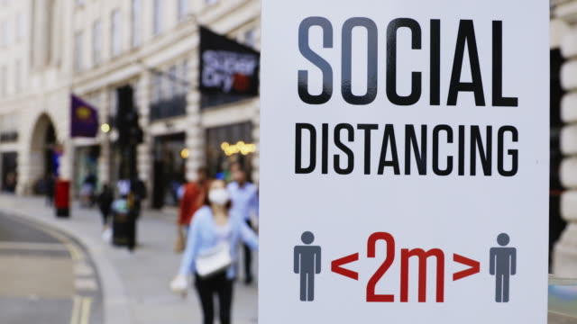 social distancing signs and notices in urban streets - safety stock-videos und b-roll-filmmaterial