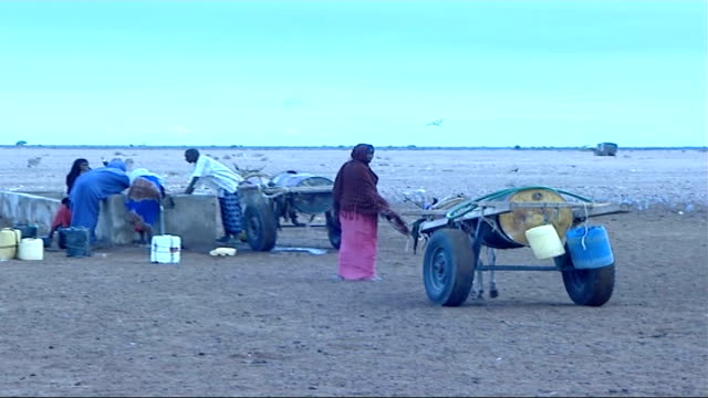 social impact of somalian refugees fleeing to kenya; donkeys carrying water containers along / women refugees filling water containers at tap /... - trough stock videos & royalty-free footage