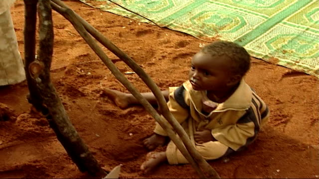 social impact of somalian refugees fleeing to kenya; women and children putting a shelter together from tree branches / baby playing in the sand /... - white点の映像素材/bロール