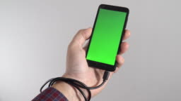 Social media obsession concept. Phone charging cable tangled around the hand