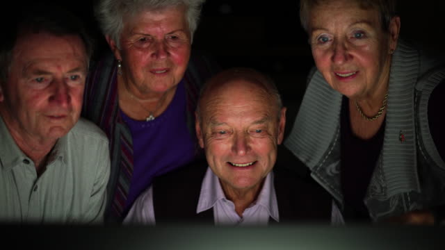 social seniors - four senior friends in front of computer laughing - pensionierung stock-videos und b-roll-filmmaterial