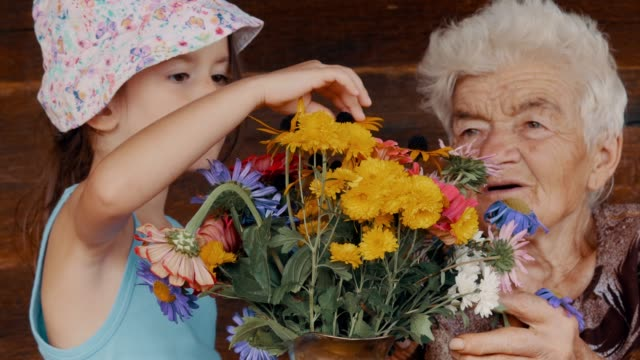 social seniors. real people. senior woman arranging flowers with granddaughter. - ethnicity stock videos & royalty-free footage