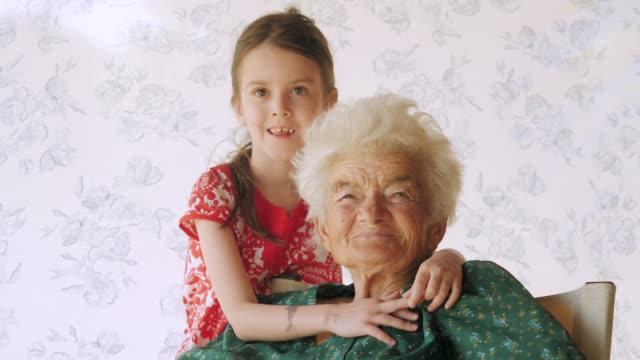 社会の高齢者。実在の人物。孫娘と年配の女性。 - 依存点の映像素材/bロール