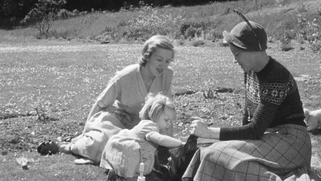 1950 montage social worker and foster mother interacting with toddler while sitting on a blanket on the lawn in front of home, and toddler running off to play and stooping to pick clover flowers / united kingdom - foster care stock videos & royalty-free footage
