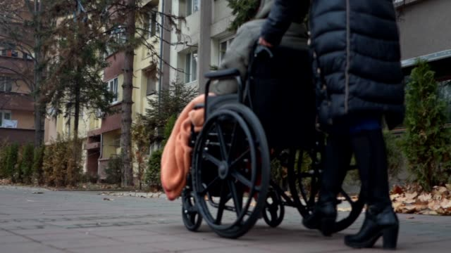 social worker transporting an elderly woman in a wheelchair - wheelchair stock videos & royalty-free footage