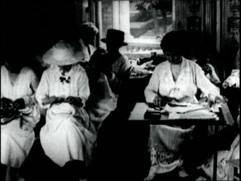vidéos et rushes de society women help with wwi war effort by sewing clothing ask public to contribute gloves hosiery and discarded articles in order to make clothing... - 1918