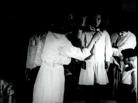 vidéos et rushes de society women sew clothing and ask public to contribute gloves hosiery and discarded articles in order to make clothing for children society women... - 1918