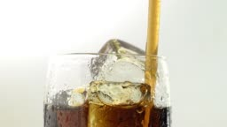 Soda in a glass with ice drink through a tube. White background. Close up