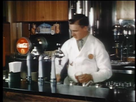 1945 soda jerk making soda quickly behind counter at soda fountain / industrial - ミルクセーキ点の映像素材/bロール