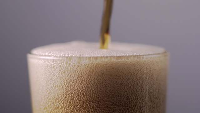Soda pours into a glass in slow motion.  Cola carbonated bubbles fizz and pour over the side of glass.