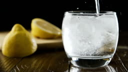 Soda water with ice cubes and lemon in the drink glass.