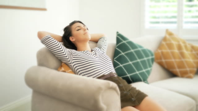 sofa relaxation. hands behind head. - mini skirt stock videos & royalty-free footage