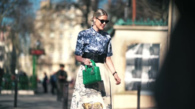Sofie Valkiers wears sunglasses earrings a blue printed shirt a large black leather belt a skirt with printed animals a green Lady Dior bag outside...