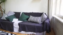 Soft beautiful cosy sofa with a book, pillows, plaid and blanket. Lagom concept