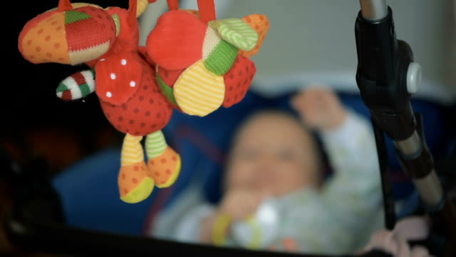 weichen tuch spielzeug in kinderwagen - ein männliches baby allein stock-videos und b-roll-filmmaterial