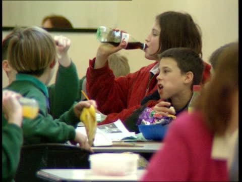soft drinks scare science bureau clipreel two schoolboys sitting drinking from bottles of orange fizzy drink schoolgirl taking bottle of coke from... - kommode stock-videos und b-roll-filmmaterial