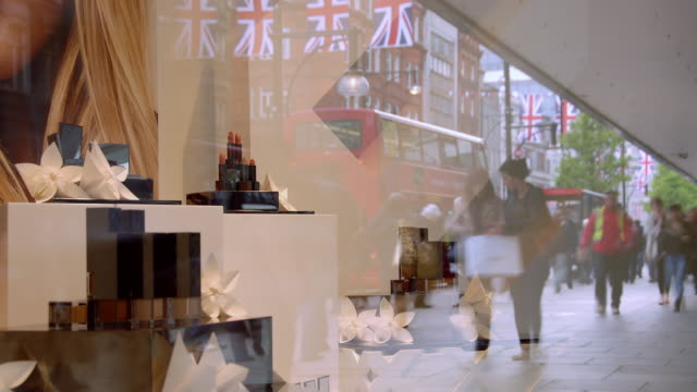 a soft focus display in an oxford street department store window crowds of shoppers and commuters on oxford street are reflected in the glass - window shopping stock videos and b-roll footage